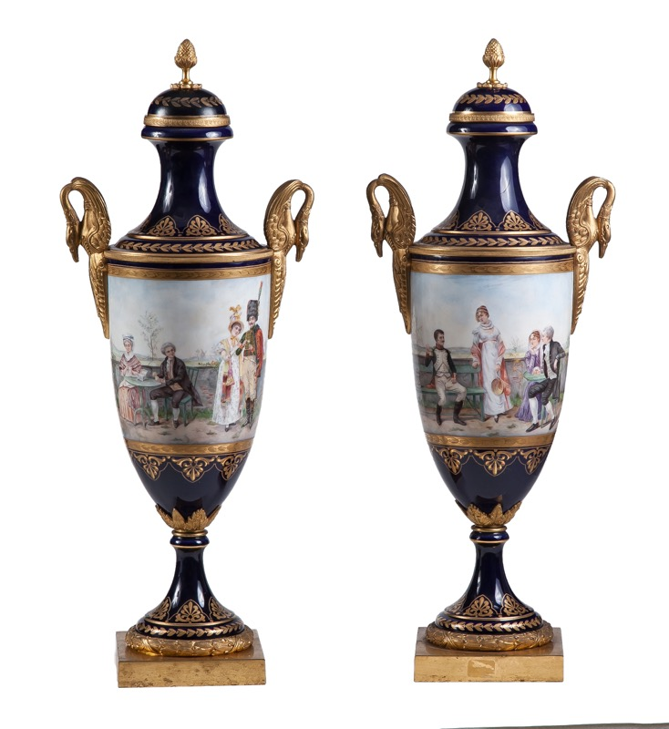 "A pair of ormolu-mounted Sèvres style porcelain blue-ground vases with galant scenes within cartouches in Empire style, 19th Century, Signed ""J. Doumas - Oudin"" 