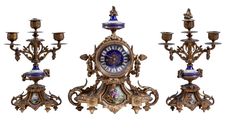A French Napoleon III porcelain and bronze garniture composed of a mantel clock and a pair of candelabras, 19th Century