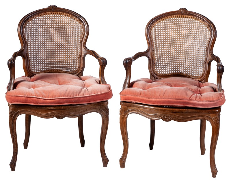 A pair of walnut canned armchairs in Louis XV style