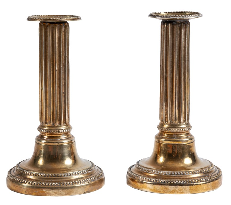 A pair of column-shaped brass candlesticks in Louis XVI style