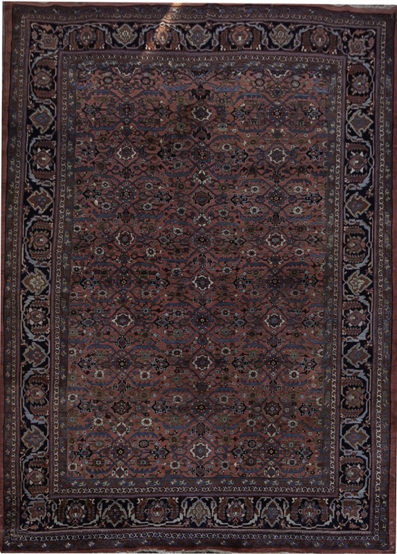 An Oriental carpet with abstract floral decoration set on red field
