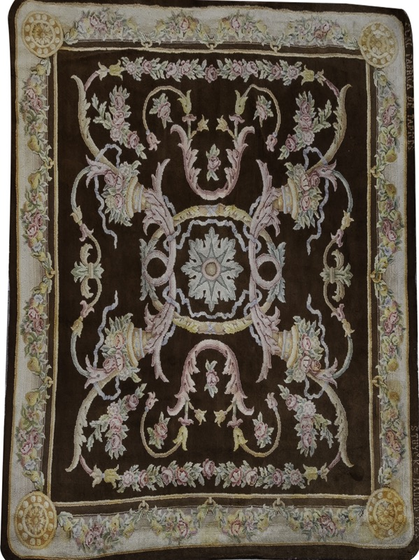 A Spanish woolen carpet with floral decoration set on brown field, Stuyck, Madrid 1923