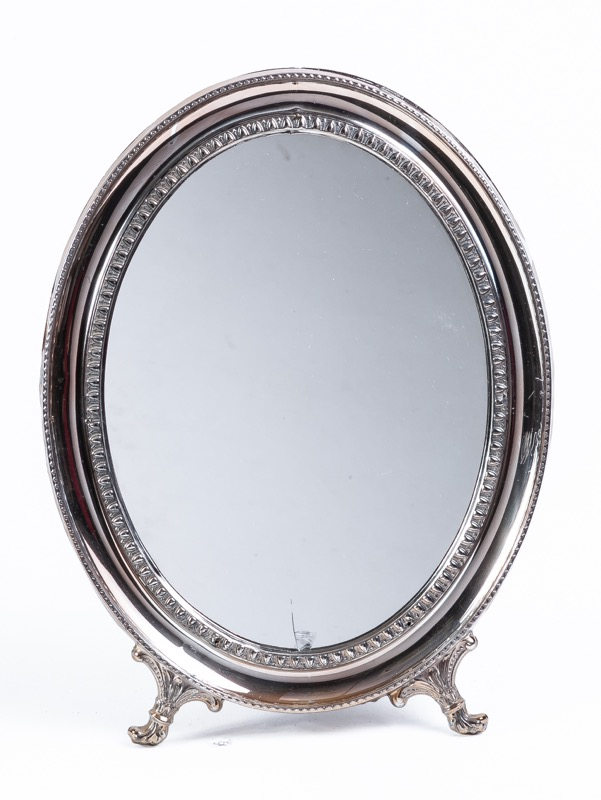 An oval silver toilet mirror