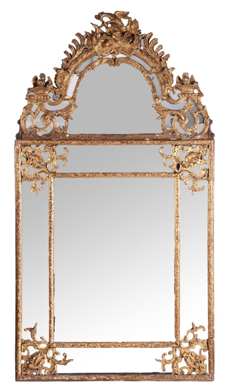A large Régence giltwood mirror topped by flower baskets, a military trophy and a bird, circa 1700