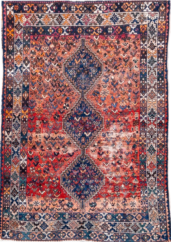 An Oriental wool rug with three medallions set on red field