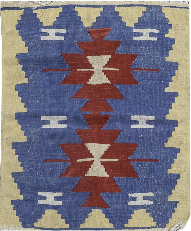 A wool kilim with red geometrical pattern set on blue field