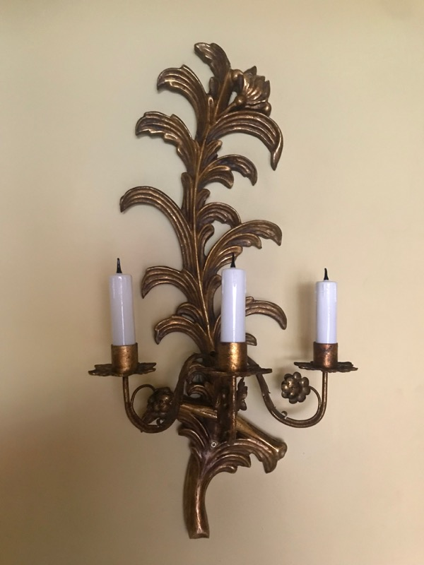 A pair of leaf-shaped giltwood three-light wall sconces